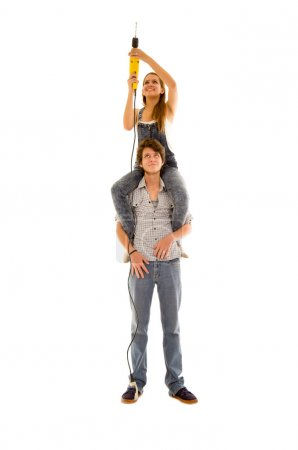 Couple wearing denim working with renovation as woman sitting on mans shoulders and holding up a power drill