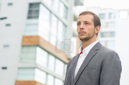 Man formal clothing in urban environment looking forward concentrated shot from front side angle