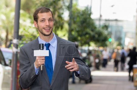 Attractive professional male news reporter wearing grey suit holding microphone, talking to camera from urban setting