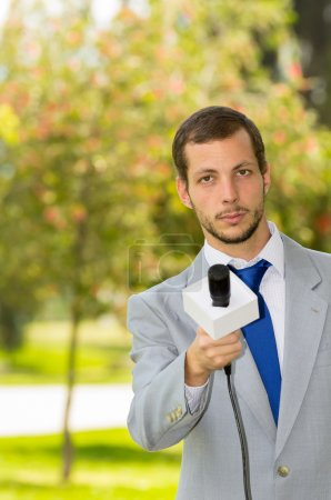 Successful handsome male news reporter wearing light grey suit working outdoors park environment holding microphone in live broadcasting