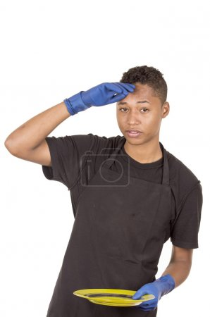 Hispanic young man wearing blue cleaning gloves holding green plate looking tired facial expression towards camera