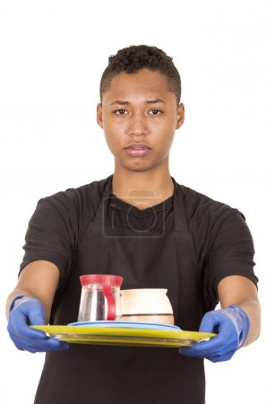 Hispanic young man wearing blue cleaning gloves carrying tray with cups and serious facial expression