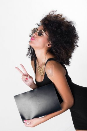 Hispanic model wearing black sexy dress and sunglasses holding blank board leaning forward making peace sign, shot from profile angle