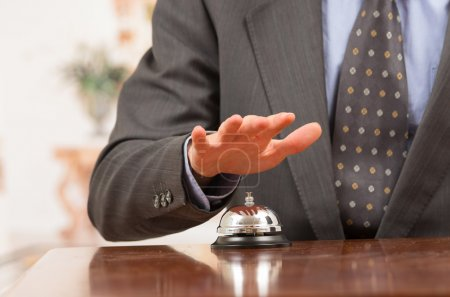 Photo for Hand of elegant man ringing hotel bell in reception desk close up selective focus - Royalty Free Image
