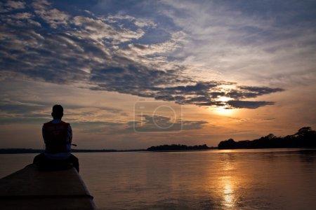 Unidentified tourist in a canoe contemplating stunning rainforest sunset, Yasuni National Park, Ecuador