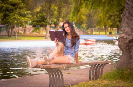 Brunette model wearing denim shirt and white shorts relaxing in park environment, sitting on bench next to lake reading book