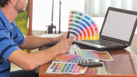Male hands holding up pantone palette, colormap spread out in front of laptop on working desk