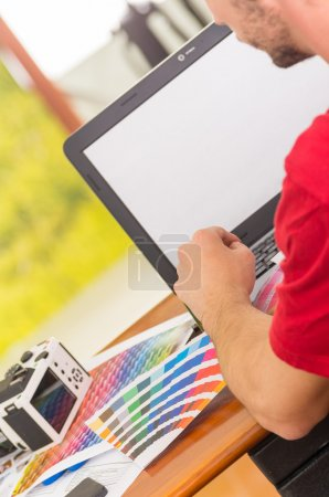 Man working on laptop with pantone palette, colormap spread out next to it