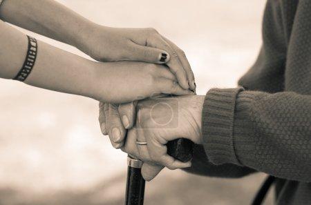 Photo pour Closeup petite-fille de grand-mère tenant par la main, édition environnement noir et blanc à l'extérieur - image libre de droit