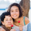 Grandmother and granddaughter posing happily toget...