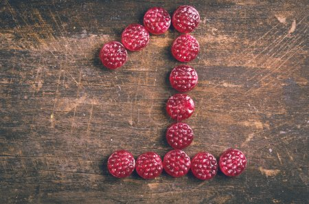 the number one shaped by raspberry hard candy on wooden surface
