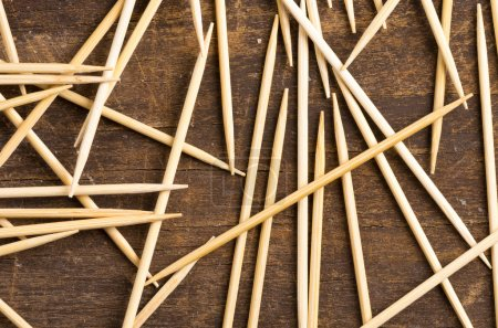Many toothpicks lying in pile facing different directions on a dark wooden surface