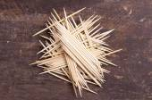 Many toothpicks tightly piled together facing different directions on dark wooden surface