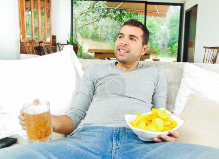 Hispanic pleased male wearing light blye sweater enjoying potato chips and beer sitting in white livingroom sofa facing camera