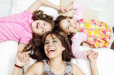 Young adorable hispanic sisters with mother lying down, heads touching and bodies spread out different directions closeup