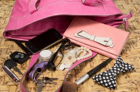 Womans purse pink color lying flat with accessories such as mobile, makeup, keys and money spread out in front