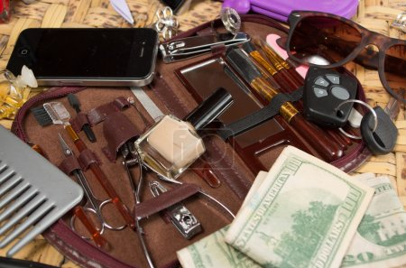 Personal belongings of typical woman, daily life concept, mobile phone, car keys, glasses and money spread out