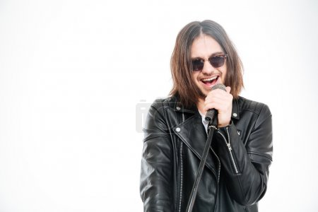 Handsome young rock singer in sunglasses singing into microphone