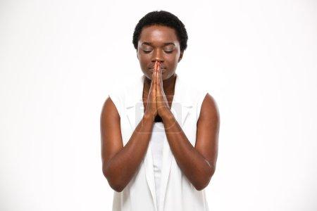 Photo pour Paisible belle afro-américaine jeune femme debout et priant sur fond blanc - image libre de droit