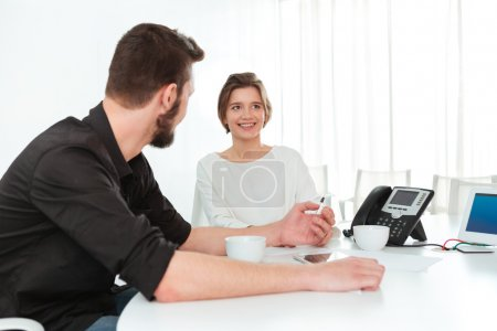 Two business people sitting and talking in office