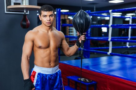 Boxer standing in gym and looking at camera