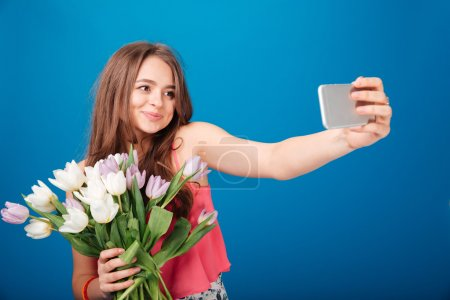 Pretty smiling young woman with bouquet of tulips taking selfie