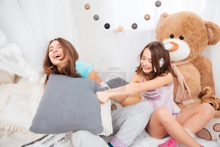 Two happy sisters laughing and fighting with pillows