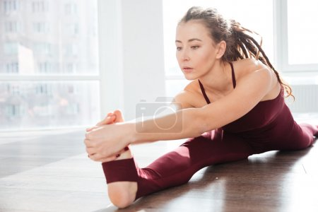 Focused young woman with dreadlocks sitting and stretching legs