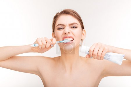 Portrait of beautiful woman holding toothpaste and brushing her teeth
