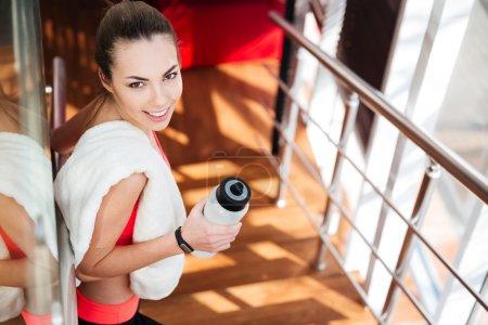 Photo pour Belle jeune sportive heureuse avec serviette blanche eau potable dans la salle de gym - image libre de droit