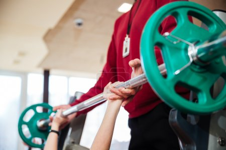 Photo for Closeup of hands of young sportswoman training with fitness instructor using barbell  in gym - Royalty Free Image
