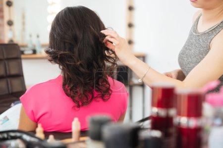 Female client with dark hair and hairdresser making hairdo