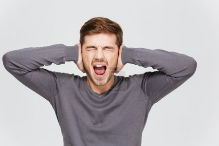 Depressed upset young man covered ears by hand and shouting