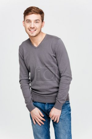 Photo for Portrait of smiling attractive young man in grey pullover and jeans standing over white background - Royalty Free Image