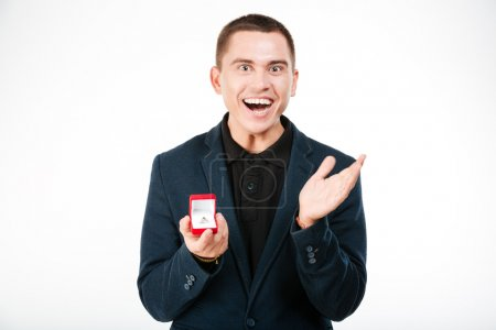 Cheerful businessman holding engagement ring