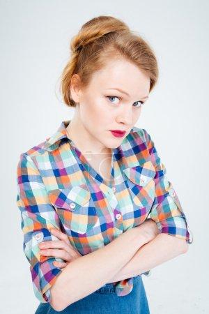 Photo pour En colère, femme debout avec les bras croisés isolé sur fond blanc - image libre de droit
