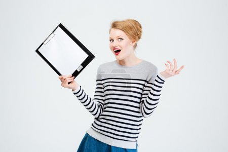 Photo for Amazed young woman holding clipboard isolated on a white background - Royalty Free Image