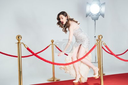 Photo for Charming woman falling on red carpet - Royalty Free Image