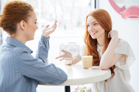 Two smiling women drinking coffee in cafe together