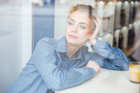 Photo for Pensive pretty young woman in blue shirt sitting and thinking in cafe - Royalty Free Image