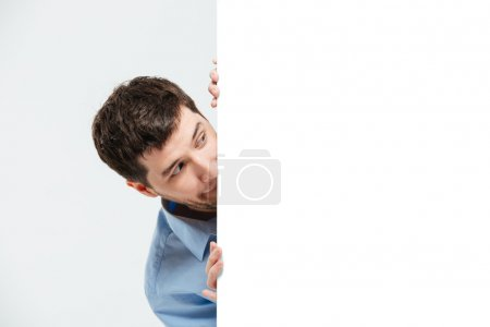 Businessman peeking from blank board