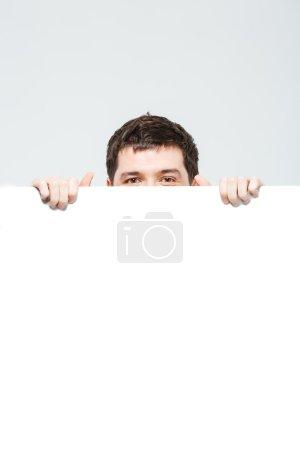Man peeking from blank board
