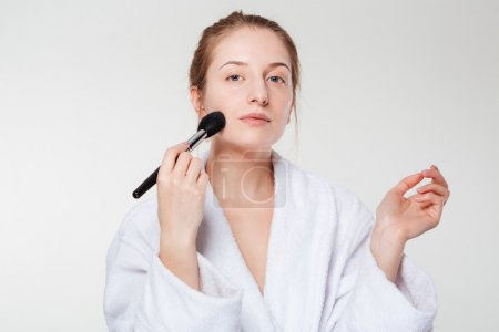 Cute woman with cosmetic brush
