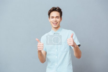 Photo for Happy casual man showing thumbs up over gray background - Royalty Free Image