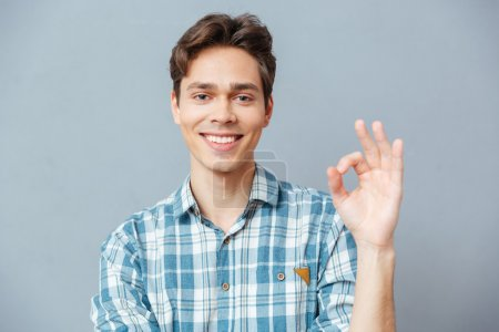 Photo pour Homme heureux montrant ok signe avec les doigts sur fond gris - image libre de droit