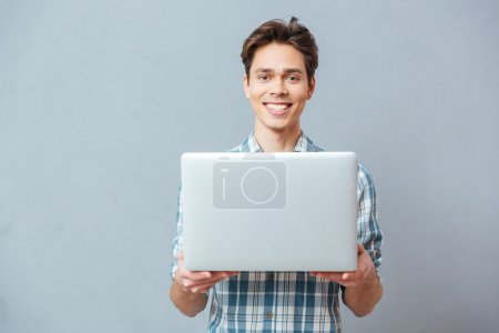Hombre feliz de pie con el ordenador portátil