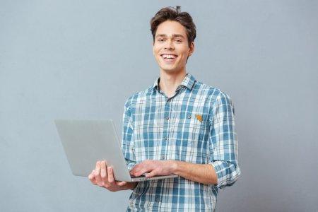 Photo pour Homme riant debout avec ordinateur portable sur fond gris et regardant la caméra - image libre de droit