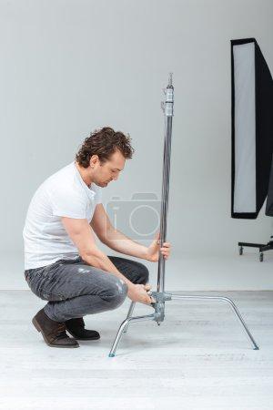 Photographer preparing lighting equipment