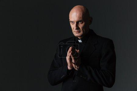 Photo pour Prêtre debout et priant sur fond noir - image libre de droit