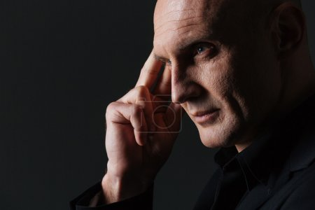 Pensive attractive businessman touching his temple and thinking